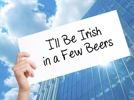 patrick: Ill Be Irish in a Few Beers Sign on white paper. Man Hand Holding Paper with text. Isolated on Skyscraper background.  Business concept. Stock Photo