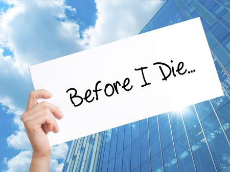Before I Die..Sign on white paper. Man Hand Holding Paper with text. Isolated on Skyscraper background.  Business concept. Stock Photo Imagens