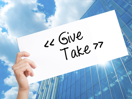 Give - Take Sign on white paper. Man Hand Holding Paper with text. Isolated on Skyscraper background.  Business concept. Stock Photo