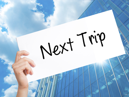 next year: Next Trip Sign on white paper. Man Hand Holding Paper with text. Isolated on Skyscraper background.   Business concept. Stock Photo
