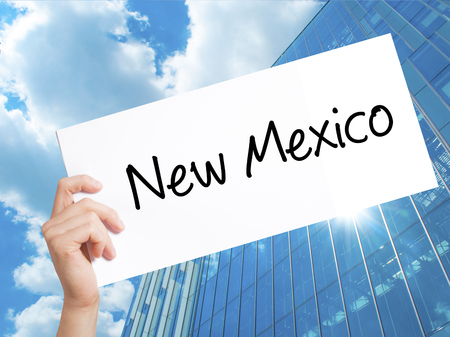 New Mexico Sign on white paper. Man Hand Holding Paper with text. Isolated on Skyscraper background.   Business concept. Stock Photo