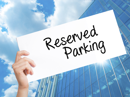 deficient: Reserved Parking Sign on white paper. Man Hand Holding Paper with text. Isolated on Skyscraper background.   Business concept. Stock Photo Stock Photo