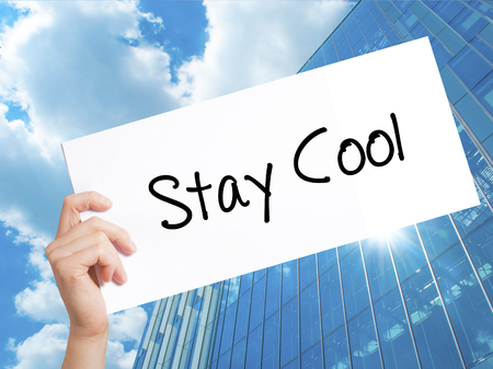 hassle: Stay Cool   Sign on white paper. Man Hand Holding Paper with text. Isolated on Skyscraper background.  Business concept. Stock Photo