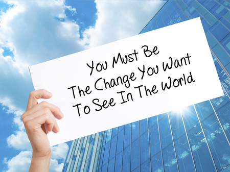 You Must Be The Change You Want To See In The World Sign on white paper. Man Hand Holding Paper with text. Isolated on Skyscraper background.   Business concept. Stock Photo