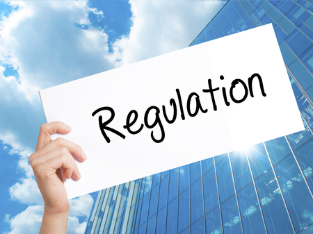 Regulation Sign on white paper. Man Hand Holding Paper with text. Isolated on Skyscraper background. Business concept. Stock Photo