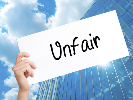 unbiased: Unfair Sign on white paper. Man Hand Holding Paper with text. Isolated on Skyscraper background.  Business concept. Stock Photo