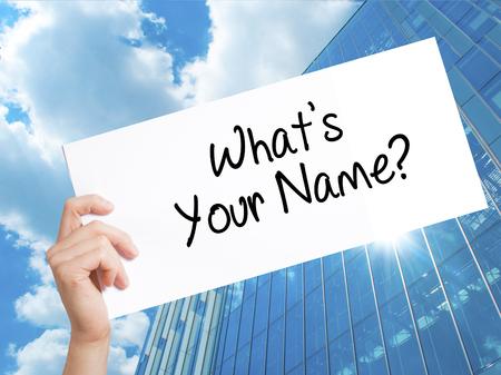 ¿Cuál es tu nombre? Firme en el Libro Blanco. Mano de hombre sosteniendo papel con texto. Aislado en el fondo del rascacielos. Concepto de negocio. Foto de stock