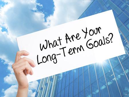 あなたの長期的な目標は何か白い紙の上に署名します。男の手を保持している紙本文。高層ビルの背景に分離されました。  ビジネス コンセプトで