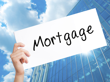 borrowing: Mortgage Sign on white paper. Man Hand Holding Paper with text. Isolated on Skyscraper background.  Business concept. Stock Photo