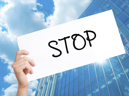 STOP  Sign on white paper. Man Hand Holding Paper with text. Isolated on Skyscraper background.  Business concept. Stock Photo 版權商用圖片