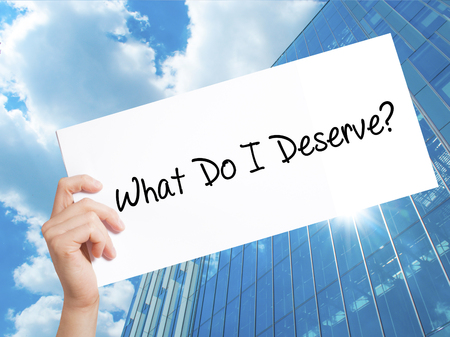 What Do I Deserve? Sign on white paper. Man Hand Holding Paper with text. Isolated on Skyscraper background.  Business concept. Stock Photo