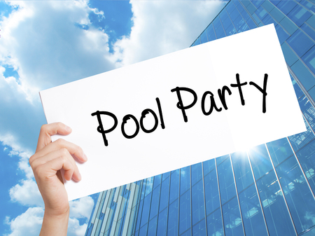 Pool Party Sign on white paper. Man Hand Holding Paper with text. Isolated on Skyscraper background.   Business concept. Stock Photo