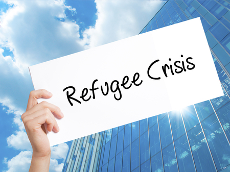 Refugee Crisis Sign on white paper. Man Hand Holding Paper with text. Isolated on Skyscraper background.  Business concept. Stock Photo