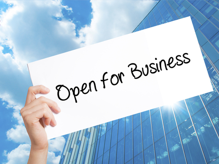 inform information: Open for Business Sign on white paper. Man Hand Holding Paper with text. Isolated on Skyscraper background.   Business concept. Stock Photo