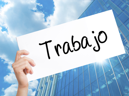 Trabajo  ( work in Spanish) Sign on white paper. Man Hand Holding Paper with text. Isolated on Skyscraper background.  Business concept. Stock Photo