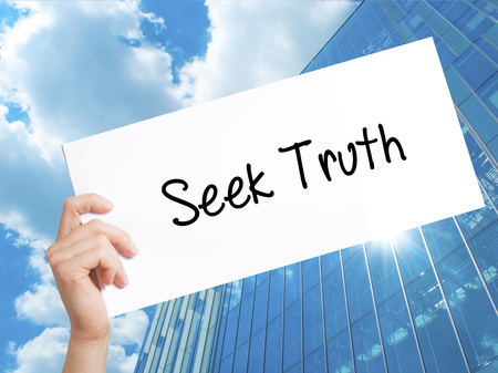 answer: Seek Truth Sign on white paper. Man Hand Holding Paper with text. Isolated on Skyscraper background.  technology, internet concept. Stock Photo