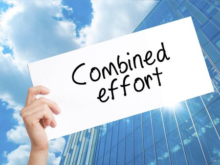 combined effort: Combined effort Sign on white paper. Man Hand Holding Paper with text. Isolated on Skyscraper background.  Business concept. Stock Photo