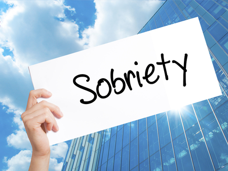 Sobriety Sign on white paper. Man Hand Holding Paper with text. Isolated on Skyscraper background.   Business concept. Stock Photo