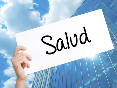Salud (Health in Spanish) Sign on white paper. Man Hand Holding Paper with text. Isolated on Skyscraper background.  Business concept. Stock Photo