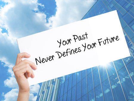 Your Past Never Defines Your Future Sign on white paper. Man Hand Holding Paper with text. Isolated on Skyscraper background.   Business concept. Stock Photo