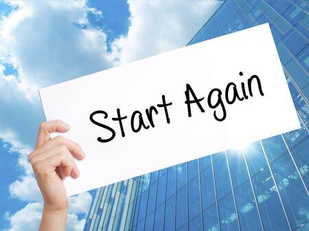 Start Again Sign on white paper. Man Hand Holding Paper with text. Isolated on Skyscraper background.  Business concept. Stock Photo