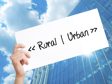 Rural - Urban Sign on white paper. Man Hand Holding Paper with text. Isolated on Skyscraper background.  Business concept. Stock Photo Stock Photo