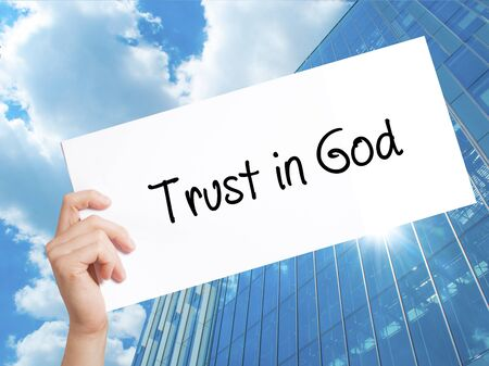 Trust in God Sign on white paper. Man Hand Holding Paper with text. Isolated on Skyscraper background.   Business concept. Stock Photo