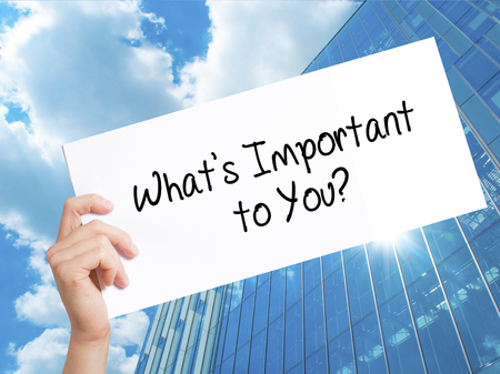 answer: Whats Important to You? Sign on white paper. Man Hand Holding Paper with text. Isolated on Skyscraper background.   Business concept. Stock Photo