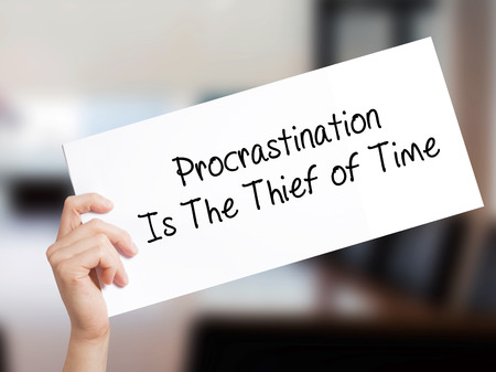 Procrastination Is The Thief of Time Sign on white paper. Man Hand Holding Paper with text. Isolated on Office background.  Business concept. Stock Photo Stock Photo