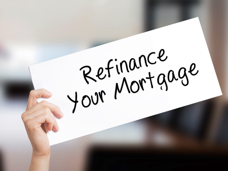 refinancing interest rates: Refinance Your Mortgage Sign on white paper. Man Hand Holding Paper with text. Isolated on Office background.  Business concept. Stock Photo