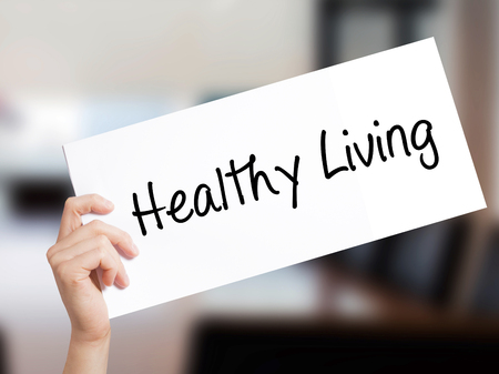Healthy Living  Sign on white paper. Man Hand Holding Paper with text. Isolated on Office background.  Business concept. Stock Photo Stock Photo