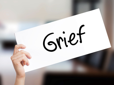 Grief Sign on white paper. Man Hand Holding Paper with text. Isolated on Office background.  Business concept. Stock Photo