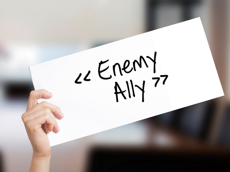 Enemy - Ally Sign on white paper. Man Hand Holding Paper with text. Isolated on Office background.  Business concept. Stock Photo Stock Photo