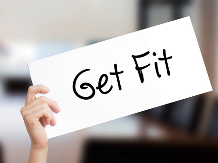 work less: Get Fit  Sign on white paper. Man Hand Holding Paper with text. Isolated on Office background.  Business concept. Stock Photo