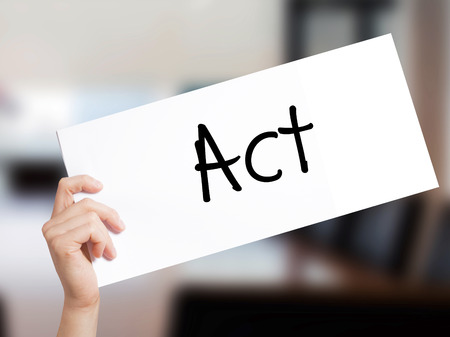 Act  Sign on white paper. Man Hand Holding Paper with text. Isolated on Office background.  Business concept. Stock Photo Stock Photo