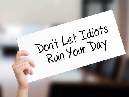 Dont Let Idiots Ruin Your Day Sign on white paper. Man Hand Holding Paper with text. Isolated on Office background.   Business concept. Stock Photo