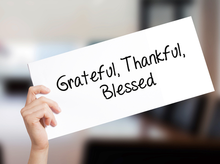 humility: Grateful Thankful Blessed Sign on white paper. Man Hand Holding Paper with text. Isolated on Office background.  Business concept. Stock Photo