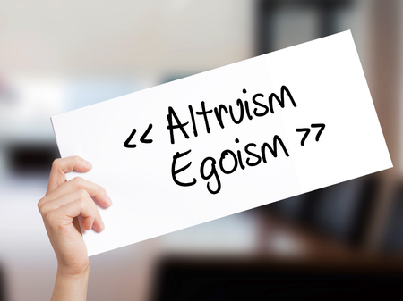 altruismo: Altruismo - Egoísmo Signo en el Libro Blanco. Mano del hombre que sostiene el papel con el texto. Aislado en fondo de la Oficina. Concepto de negocio. Foto de stock