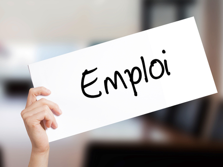 Emploi (Employment in French) Sign on white paper. Man Hand Holding Paper with text. Isolated on Office background.  Business concept. Stock Photo Imagens