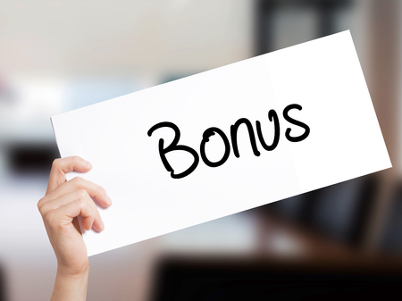Bonus Sign on white paper. Man Hand Holding Paper with text. Isolated on Office background.  Business concept. Stock Photo