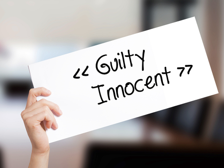 fair trial: Guilty - Innocent Sign on white paper. Man Hand Holding Paper with text. Isolated on Office background.  Business concept. Stock Photo