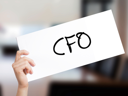 CFO (Chief Financial Officer) Sign on white paper. Man Hand Holding Paper with text. Isolated on Office background.  Business concept. Stock Photo Stock Photo