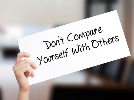 differentiation: Dont Compare Yourself With Others Sign on white paper. Man Hand Holding Paper with text. Isolated on Office background.  Business concept. Stock Photo