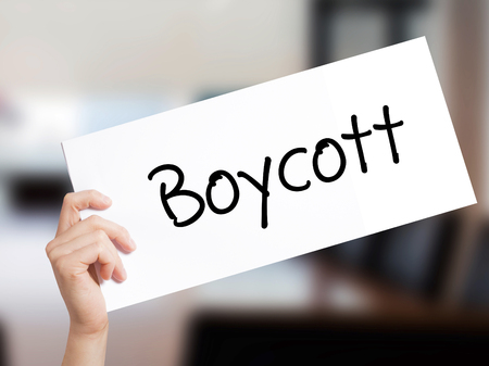 denying: Boycott Sign on white paper. Man Hand Holding Paper with text. Isolated on Office background.  Business concept. Stock Photo