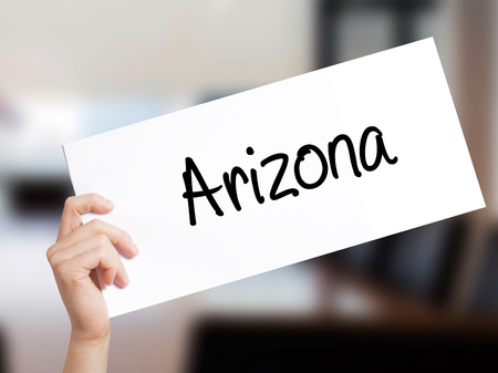 stone of destiny: Arizona  Sign on white paper. Man Hand Holding Paper with text. Isolated on Office background.  Business concept. Stock Photo