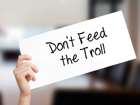 Dont Feed the Troll Sign on white paper. Man Hand Holding Paper with text. Isolated on Office background.  Business concept. Stock Photo