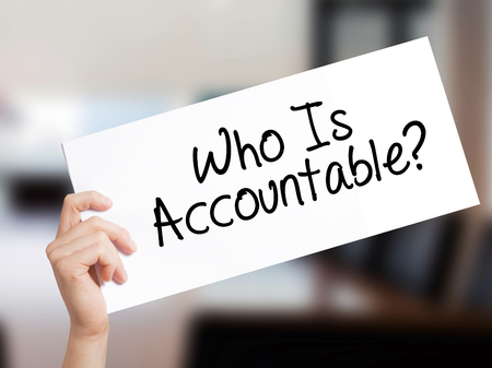 answer: Who Is Accountable? Sign on white paper. Man Hand Holding Paper with text. Isolated on Office background.  Business concept. Stock Photo
