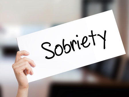 Sobriety Sign on white paper. Man Hand Holding Paper with text. Isolated on Office background.   Business concept. Stock Photo