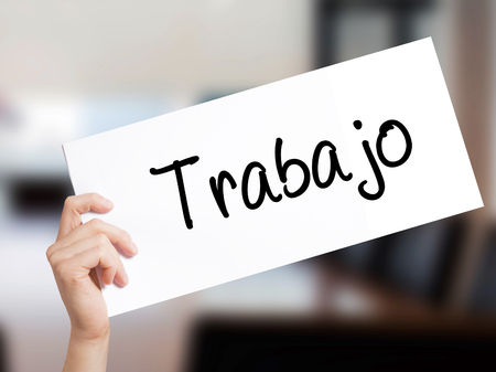 Trabajo  ( work in Spanish) Sign on white paper. Man Hand Holding Paper with text. Isolated on Office background.  Business concept. Stock Photo