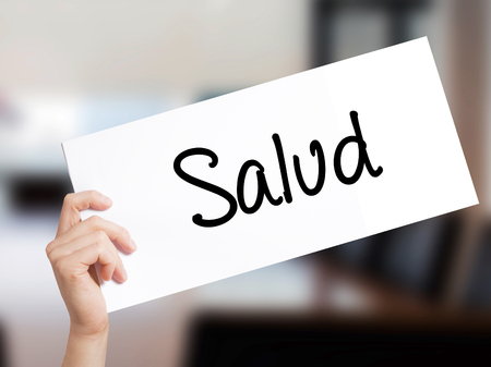 Salud (Health in Spanish) Sign on white paper. Man Hand Holding Paper with text. Isolated on Office background.  Business concept. Stock Photo Stock Photo